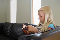 Girl (7-9) sitting on sofa reading book