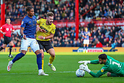 Brentford goalkeeper David Raya Martin (1) makes a save from Millwall forward Tom Bradshaw (9) challenged by Brentford defender Julian Jeanvier (23) during the EFL Sky Bet Championship match between Brentford and Millwall at Griffin Park, London, England on 19 October 2019.