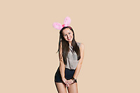 Portrait of a happy young woman wearing bunny ears posing over colored background