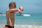 Boy playing with sand on Garrapatero Beach, Santa Cruz Island, Galapagos Islands, Ecuador.
