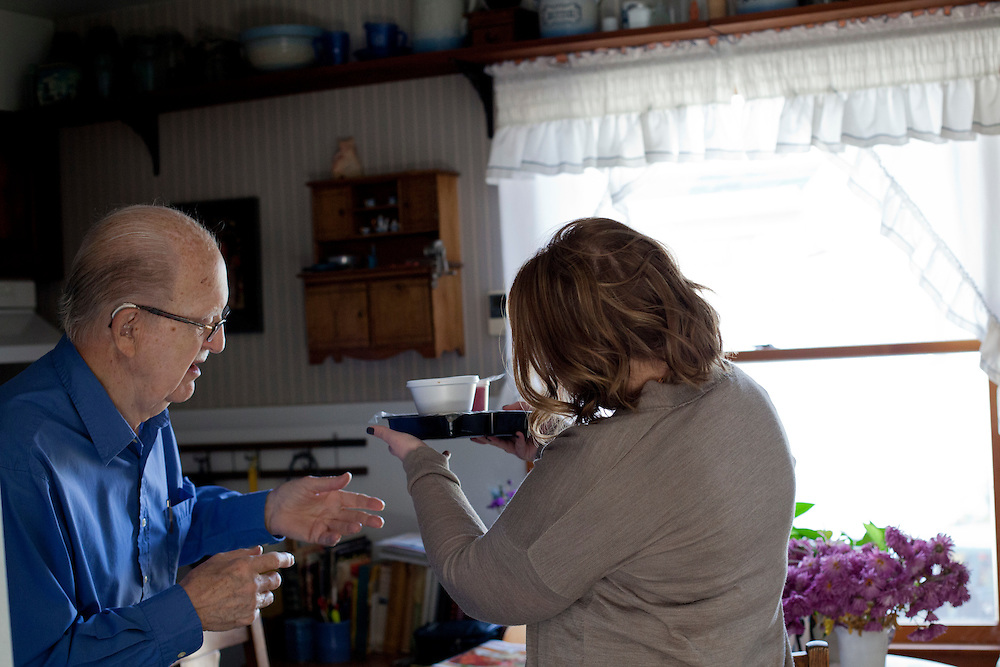 William Ortmayer takes his Meals on Wheels lunch from Horizons volunteer coordinator Anna Ronnebaum at his home in Cedar Rapids, Iowa on Thursday, November 19, 2015. (Rebecca F. Miller/Freelance for The Gazette)