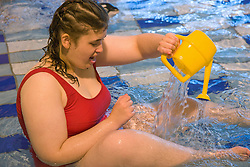 Day service users with learning disability playing with a watering can in the water at a local swimming pool,