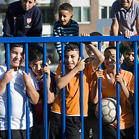 Nederland Rotterdam 18-09-2009 20090918 Foto: David Rozing       Jonge allochtone kinderen van divers komaf poseren op speelpleintje in achterstandswijk Crooswijk. 2 van hen dragen een oranje voetbal tshirt.       Young boys posing, playing on playcourt playground  deprived area / projects This area is on a list with projects which need help of the government because of degradation in the area etc.      .Foto: David Rozing