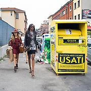 Il Quinto giorno della Settimana della Moda a Milano: buyers e modelli camminano vicino al contenitore della raccolta dei vestiti usati destinati alle persone povere.<br /> <br /> The fifth day of Milan Fashion Week: fashion buyers and models walking close a container of second hand clothes destined to poor people