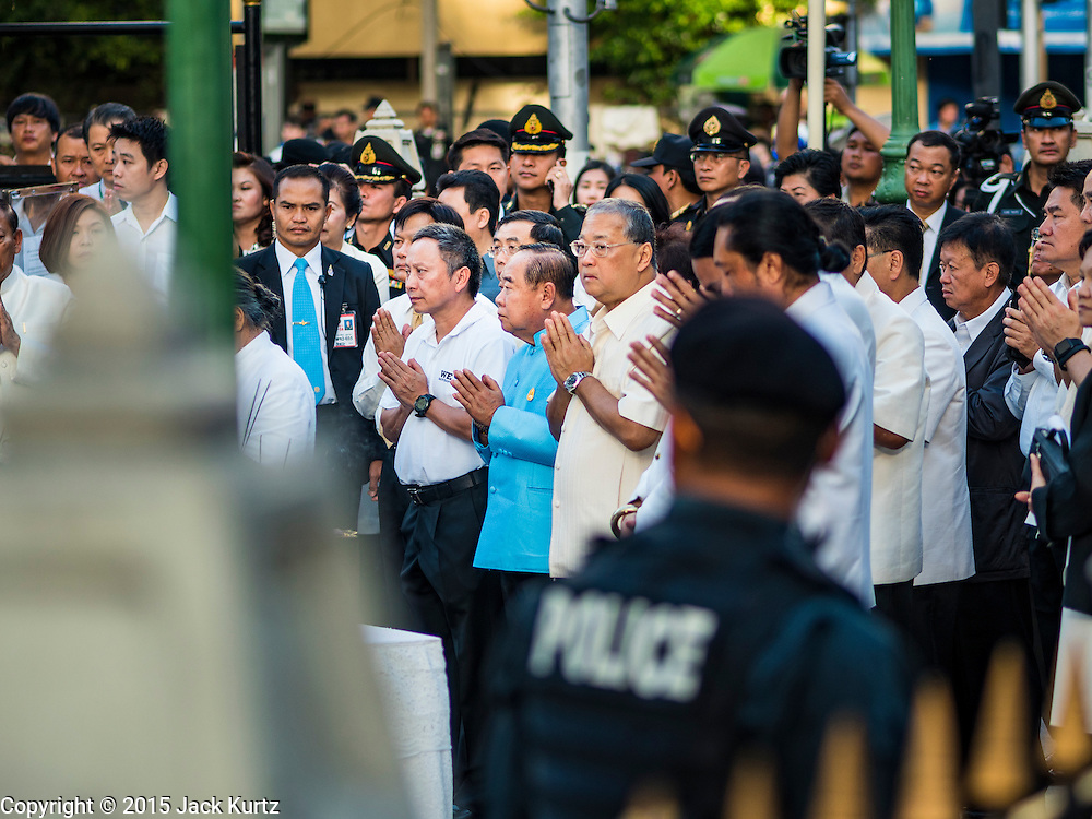 21 AUGUST 2015 - BANGKOK, THAILAND:  Bangkok Governor SUKHUMBHAND PARIBATRA, center right wearing glasses, and Deputy Prime Minister PRAWIT WONGSUWAN, next to Sukhumbhand in blue tunic, participate in a prayer at the Erawan Shrine Friday. The Bangkok Metropolitan Administration (BMA) held a religious ceremony Friday for the Ratchaprasong bomb victims. The ceremony started with a Brahmin blessing at Erawan Shrine, which was the target of a bombing Monday night. After the blessing people went across the street to the plaza in front of Central World mall for an interfaith religious service. Theravada Buddhists, Mahayana Buddhists, Muslims, Sikhs, Hindus, and Christians participated in the service. Life at the shrine, one of the busiest in Bangkok, is returning to normal. Friday the dancers and musicians who perform at the shrine resumed their schedules.      PHOTO BY JACK KURTZ