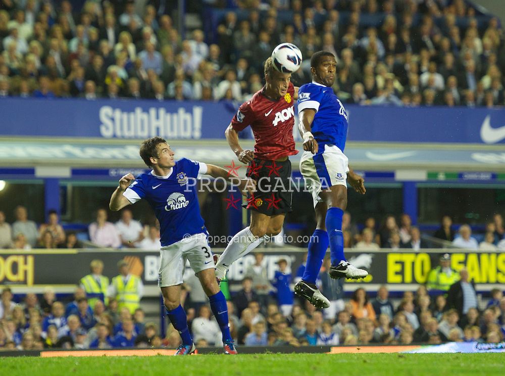 LIVERPOOL, ENGLAND - Monday, August 20, 2012: Manchester United's Nemanja Vidic in action against Everton's Sylvain Distin during the Premiership match at Goodison Park. (Pic by David Rawcliffe/Propaganda)