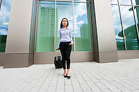 Full length of young businesswoman with suitcase on sidewalk against building