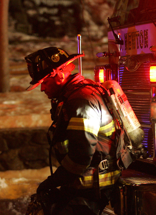 Newton, MA 02/21/2011.A Newton firefighter takes a rehab break while combating a 4 alarm structure fire at 56 Waverly Ave in Newton early Monday morning.  One occupant was transported to Newton-Wellesley Hospital and another one remained unaccounted for, officials said..Alex Jones / For The Newton TAB