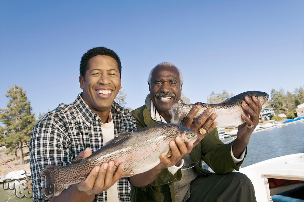 Middle-aged man and son showing fishes smiling (portrait)