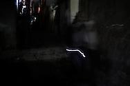 People walking in total darkness finding their way with a small torch. Persone camminano in una strada totalmente buia aiutandosi con una piccola lampadina.