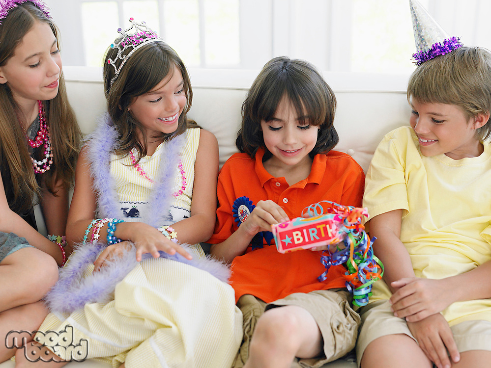 Four children (7-12) sitting on sofa at birthday party one opening present