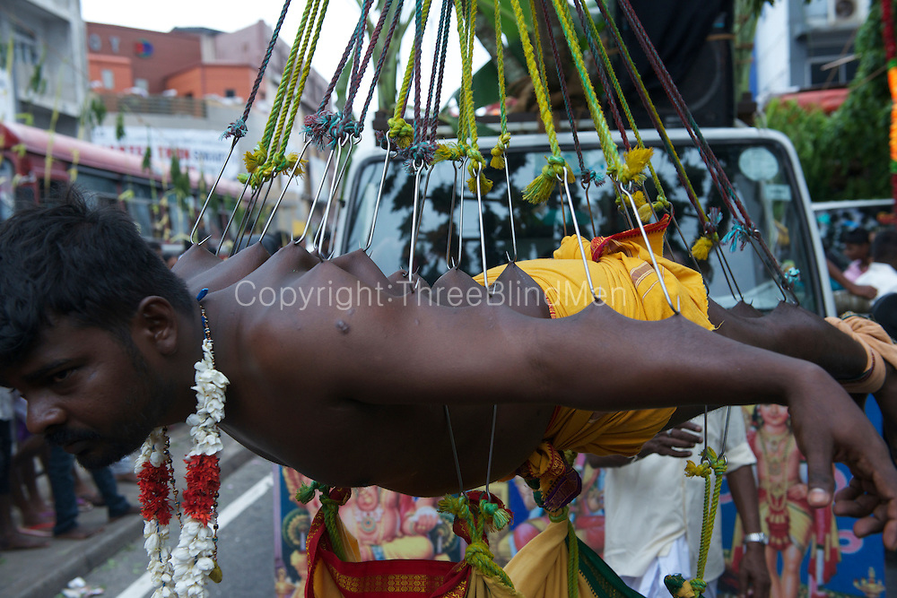 Fulfilling a vow, a penitent suspended by hooks.<br />