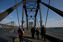 Tourists walk along the Yalu River 'Broken' Bridge where the Sino-Korean Friendship Bridge is seen beside connecting Sinuiju, North Korea, along the Yalu River in the Chinese city of Dandong, Liaoning Province, China on 06 April 2013. North Korean leader Kim Jong-un has ordered the country's military to increase artillery production, a televised report out of Pyongyang showed 06 April.