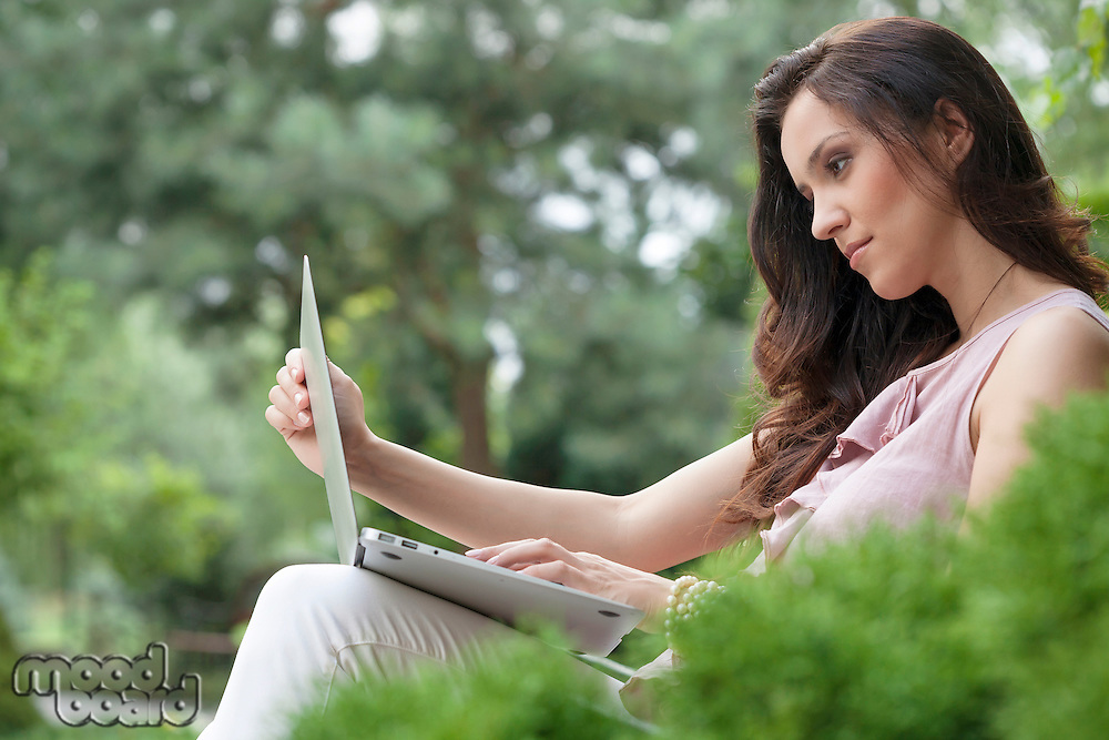 Side view of beautiful young woman using laptop in park