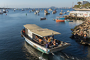 A coastal fishing boat heads out in Guanabara Bay in the Urca neighborhood in Rio de Janeiro, Brazil.