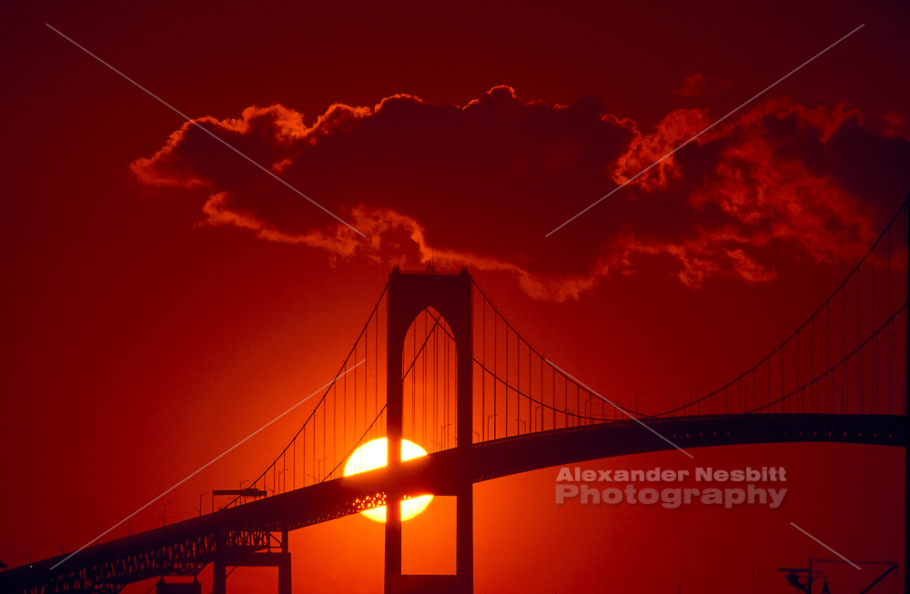 USA, Newport, RI - Setting sun centered behind tower of Newport Bridge with red filter.