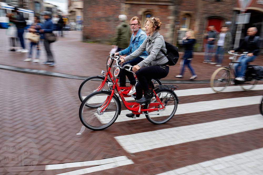 Een man en vrouw fietsen op een MacBike huurfiets over het Muntplein in Amsterdam.<br /> <br /> A man and woman cycle on a MacBike rental bike at the Munt Square in Amsterdam.