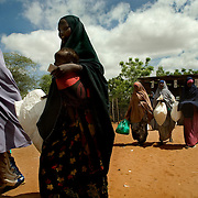 Somali refugees walk towards a food distribution at the Hagadera refugee camp in  Dadaab, Kenya. Continuing violence in Somalia has led to more and more Somalis seeking refuge across the border in Kenya, but UNHCR is struggling to cope with the thousands of new arrivals at the camps who need shelter, food, and medical attention. .
