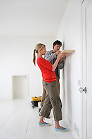 Couple putting up shelf in new home