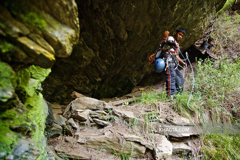 Bharat Bhushan, a Mountaneer, spreading a rope before climbing through a Chimney Rocks in Chopal region of Shimla, Himachal Pradesh, India