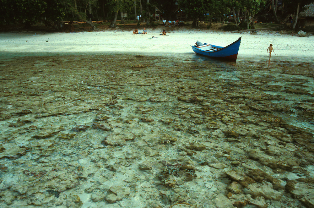 Iboh, Pulau Weh, Sumatra, Indonesia. View from off shore over coral to see beached boat and young naked child playing in the water