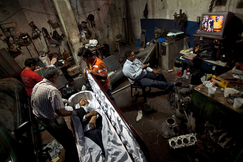 """""""Don Carlos"""", the owner of """"Valles del Sol"""", a car repair shop turned into funeral home, prepares the body of a murdered man to be buried while other funeral service salesmen watch a comic show on T.V., Guatemala City, Saturday, Aug 29,  2009. Guatemala's constant streak of murders ,17-a-day,  provide a steady flow of customers to unregulated  funeral homes, where funeral workers can embalm corpses in the back of auto repair shop or rush to crime scenes to gather information that will allow them to locate, notify and make a sales pitch to the bereaved relatives."""