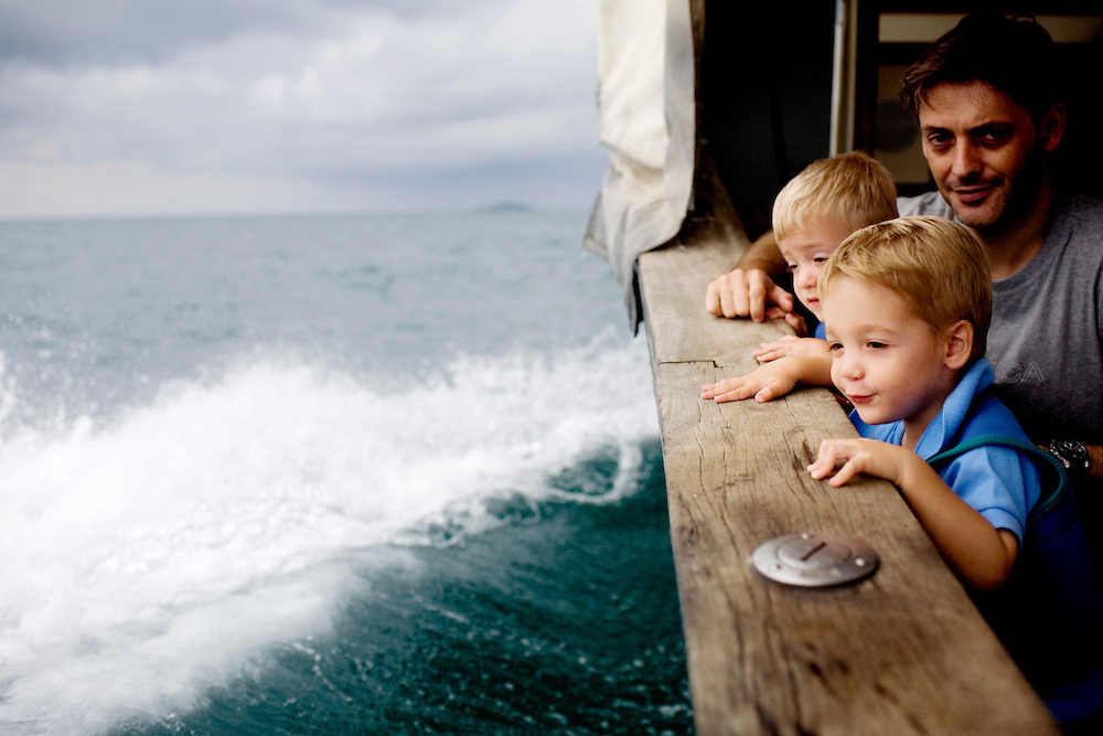 Twin brothers Niels and Emile Croly-Labourdette, 2, with their father, Nicolas, of Singapore, watch the spray of water from Nikoi Island's ferry, from Kawal, Bintan, to Nikoi, Indonesia, on Sunday, April 18, 2010.