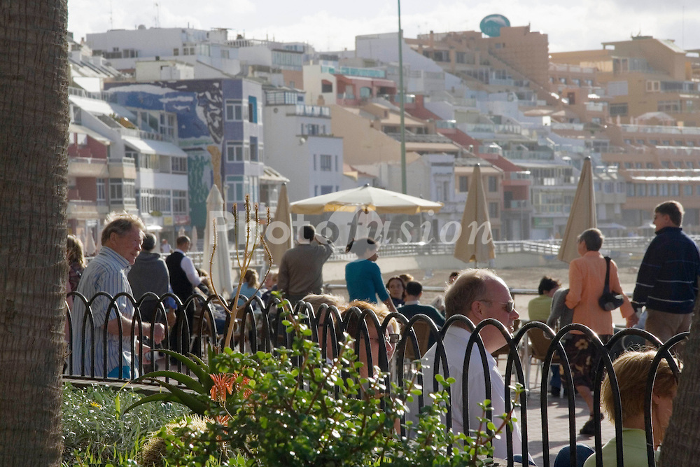 People sitting on the sea front in the Canary Islands,