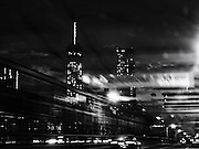 View of the Freedom Tower from the Brooklyn Bridge, with yellow taxi cabs and urban skyline with skyscrapers lit up at night, New York City, NY. Original black and white fine art photograph as shot in camera with an abstract feel and a feeling of motion taken from a moving car traveling over the bridge.