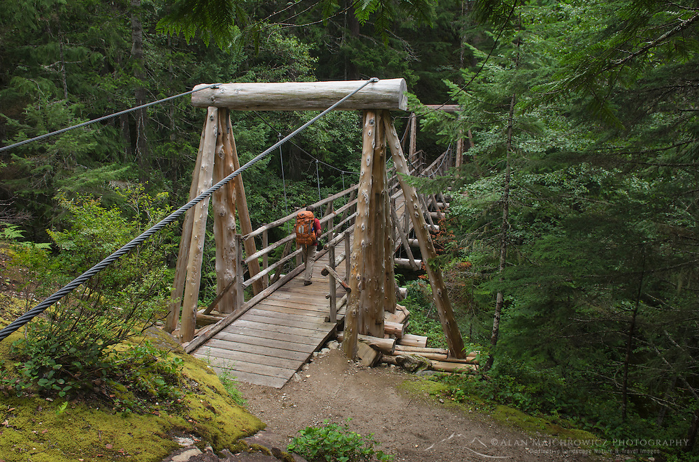 Backpacker on Suspension Bridge over Canyon Creek, Suiattle River Trail, Glacier Peak Wilderness North Cascades Washington