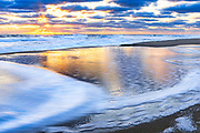 The sun peeks out from a bank of clouds at sunrise at Kitty Hawlk beach on the Outer Banks of NC.