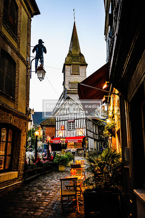 Restaurants in the Rue des Lingots with St Catherine's Church in the background in Honfleur, Normandy, France