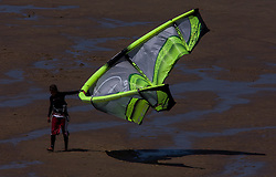 A kitesurfer floats his kite along the beach. (Photo © Jock Fistick)
