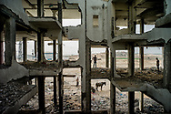 People looking for pieces of concrete to take them away in the cart in a building destroyed during the war last year in in Beit Lahiya, Gaza. The concret is later smashed and sold as construction material. August 3, 2015. Photo/Tomas Munita
