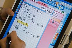 Teacher writing in Chinese Mandarin on tablet pc,