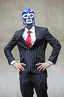 Young businessman in pinstripes suit and wrestling mask over gray background