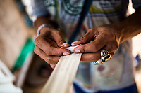 Sompon Samrong rolls up bandages for his son's hands before a Muay Thai fight outside of Bangkok, Thailand.