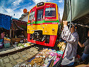 27 SEPTEMBER 2016 - BANGKOK, THAILAND:  A woman who works in the market in the Samut Songkhram train station watches a train leave the station. The train from Baen Laem to Samut Songkhram (Mae Khlong) recently resumed service. The 33 kilometer track was closed for repair for almost a year. In Samut Songkhram, the train passes over the market. Vendors pull their stands out of the way and people step out of the way as the train passes through the market. It is one of the most famous train stations in Thailand and has become an important tourist attraction in the community.    PHOTO BY JACK KURTZ