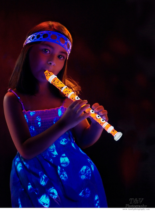 Young girl with a glowing headband plays a glowing flute.Black light