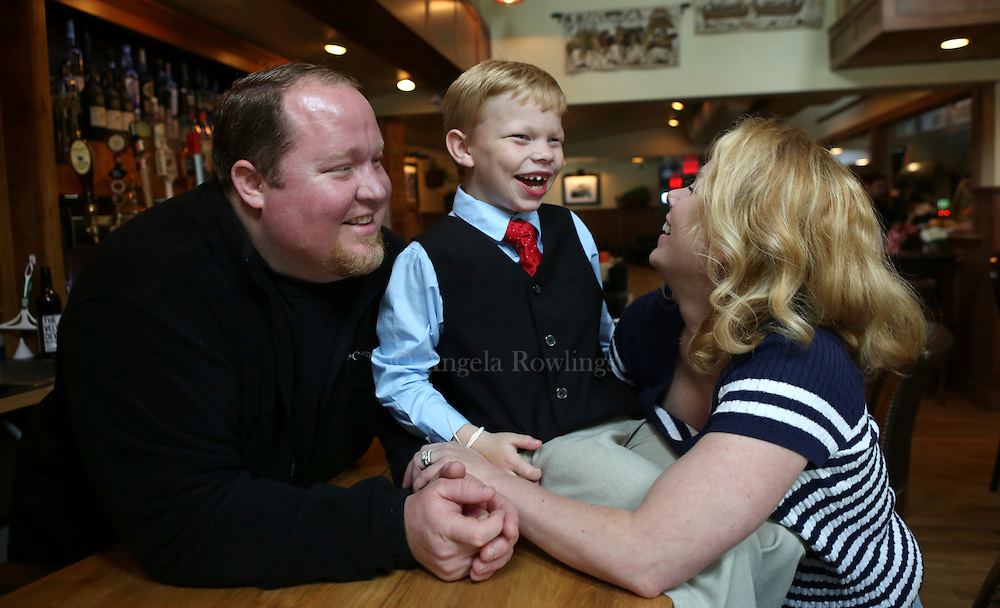 (Falmouth, MA - 5/28/15) Charlie Rickard, 8, who works weekends as a maitre d' in his parents' Falmouth restaurant, Bear in Boots, is seen with his dad, Gates Rickard and his mom, Kate Rickard, Thursday, May 28, 2015.  Staff photo by Angela Rowlings.
