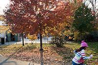 """9 Novembre, 2008. Brooklyn, New York.<br /> <br /> Una bambina corre davanti all'entrata del parco giochi di Prospect Park a Park Slope, Brooklyn, NY. Park Slope, spesso definito dai newyorkesi come """"The Slope"""", è un quartiere nella zona ovest di Brooklyn, New York, e confinante con Prospect Park.  Park Slope è un quartiere benestante che ha il maggior numero di nascite, la qualità della vita più alta e principalmente abitato da una classe media di razza bianca. Per questi motivi molte giovani coppie e famiglie decidono di trasferirsi dalle altre municipalità di New York a Park Slope. Dal punto di vista architettonico, il quartiere è caratterizzato dai brownstones, un tipo di costruzione molto frequente a New York, e da Prospect Park.<br /> <br /> ©2008 Gianni Cipriano for The New York Times<br /> cell. +1 646 465 2168 (USA)<br /> cell. +1 328 567 7923 (Italy)<br /> gianni@giannicipriano.com<br /> www.giannicipriano.com"""