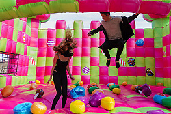 More London Place, London, March 3rd 2016. PICTURED: UCL students Emma Pujol-Hodge and Diego Ospina enjoy the exuberance of the bouncy castle.<br /> A jelly-themed, adults-only bouncy castle which has been created to celebrate the launch of Candy Crush Jelly Saga, opens on London&rsquo;s Southbank. The multi-sensory bouncy castle especially designed for grown-ups,  marks the latest instalment of the new mobile game, Candy Crush Jelly Saga. The bouncy castle brings to life elements of the jelly-themed game and will be open to the public for free. The castle, which appears to be made up of cubes of lime and raspberry jelly, will encompass a range of multi-sensory elements, emitting fragrant, raspberry jelly-scented clouds from within its walls and making noises from the game when jumpers bounce on certain candy squares. It will also replicate the game&rsquo;s new competitive element and introduce visitors to Candy Crush Jelly Saga&rsquo;s latest character, the Jelly Queen.
