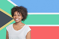 Portrait of young African American woman in white t-shirt smiling against South African flag