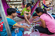 19 JANUARY 2014 - BANGKOK, THAILAND:  Members of the cast eat lunch backstage while the crew sets up the stage before a mor lam show in Khlong Tan Market in Bangkok. Mor Lam is a traditional Lao form of song in Laos and Isan (northeast Thailand). It is sometimes compared to American country music, song usually revolve around unrequited love, mor lam and the complexities of rural life. Mor Lam shows are an important part of festivals and fairs in rural Thailand. Mor lam has become very popular in Isan migrant communities in Bangkok. Once performed by bands and singers, live performances are now spectacles, involving several singers, a dance troupe and comedians. The dancers (or hang khreuang) in particular often wear fancy costumes, and singers go through several costume changes in the course of a performance. Prathom Bunteung Silp is one of the best known Mor Lam troupes in Thailand with more than 250 performers and a total crew of almost 300 people. The troupe has been performing for more 55 years. It forms every August and performs through June then breaks for the rainy season.              PHOTO BY JACK KURTZ