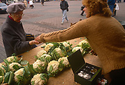 Six months after the fall of the Berlin Wall, an elderly lady is handed her change after buying some cauliflowers at a market stall, on 1st June 1990, in Leipzig, eastern Germany (former DDR).