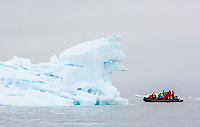 A passenger filled Zodiak cruises amongst ice flows near Pleneau Island.   Antarctic Peninsula, Antarctica