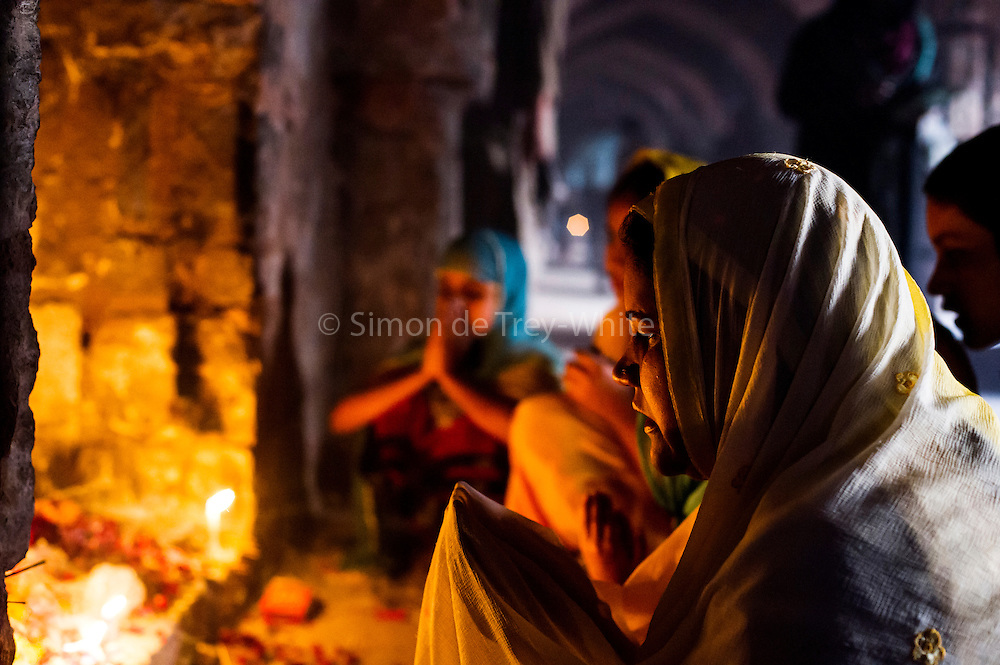19th March 2015, New Delhi, India. A woman prays to Djinns in the hopes of getting her wishes granted in the ruins of Feroz Shah Kotla in New Delhi, India on the 19th March 2015<br /> <br /> PHOTOGRAPH BY AND COPYRIGHT OF SIMON DE TREY-WHITE a photographer in delhi<br /> + 91 98103 99809. Email: simon@simondetreywhite.com<br /> <br /> People have been coming to Firoz Shah Kotla to leave written notes and offerings for Djinns in the hopes of getting wishes granted since the late 1970's. Jinn, jann or djinn are supernatural creatures in Islamic mythology as well as pre-Islamic Arabian mythology. They are mentioned frequently in the Quran  and other Islamic texts and inhabit an unseen world called Djinnestan. In Islamic theology jinn are said to be creatures with free will, made from smokeless fire by Allah as humans were made of clay, among other things. According to the Quran, jinn have free will, and Iblīs abused this freedom in front of Allah by refusing to bow to Adam when Allah ordered angels and jinn to do so. For disobeying Allah, Iblīs was expelled from Paradise and called &quot;Shayṭān&quot; (Satan).They are usually invisible to humans, but humans do appear clearly to jinn, as they can possess them. Like humans, jinn will also be judged on the Day of Judgment and will be sent to Paradise or Hell according to their deeds. Feroz Shah Tughlaq (r. 1351&ndash;88), the Sultan of Delhi, established the fortified city of Ferozabad in 1354, as the new capital of the Delhi Sultanate, and included in it the site of the present Feroz Shah Kotla. Kotla literally means fortress or citadel.