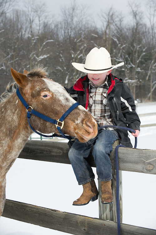 Young boy sitting on fence enjoying himself with his Appaloosa horse buddy, five years old dressed in white cowboy hat and western wear, winter snow scene in Pennsylvania, PA, USA.