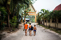 Young children walk through a temple complex in Rayong, Thailand after Muay Thai training.