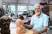 An image of a recovering stroke patient at work in his art studio. Image is part of a library of work shot for a local hospital chain spotlighting their rehabilitation services.